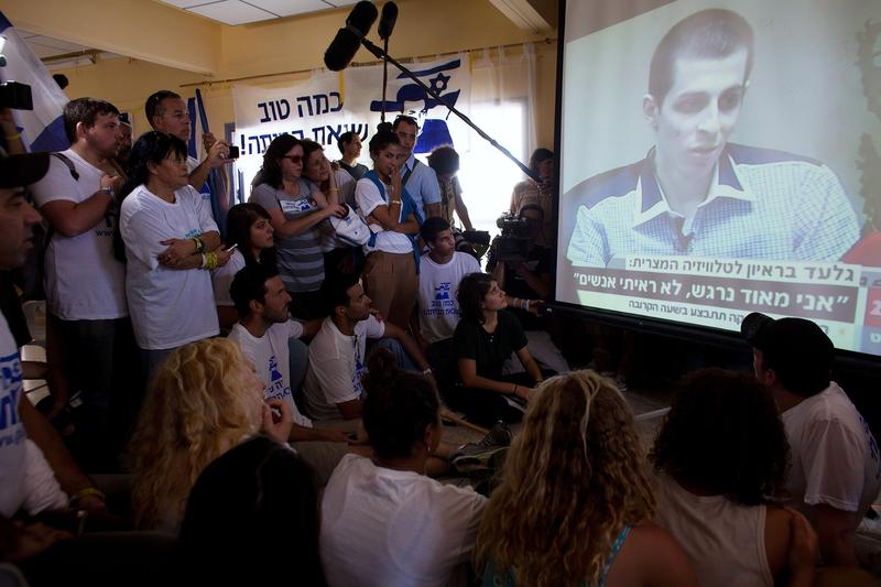 Israelis watch the first images of Israeli Defense Forces soldier Gilad Shalit on TV following his release on October 18, 2011 in Mitzpe Hila, Israel.