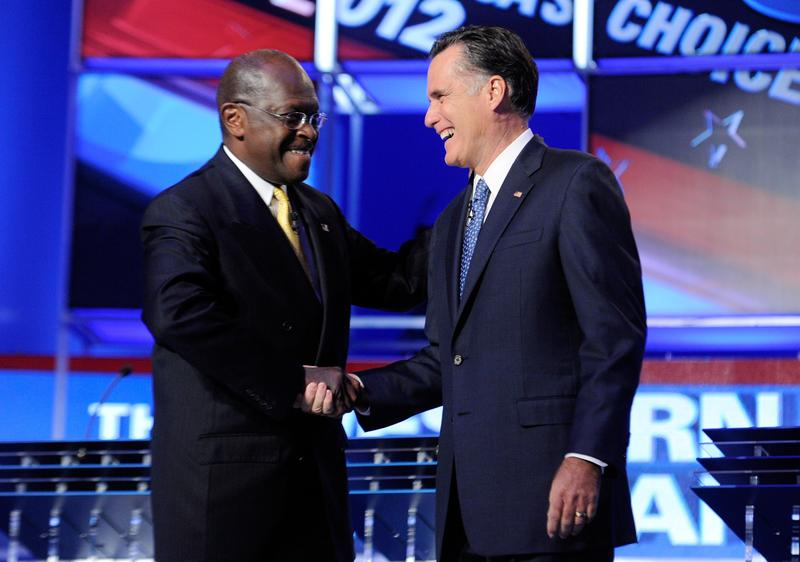 Herman Cain and Mitt Romney greet each other at the GOP debate.