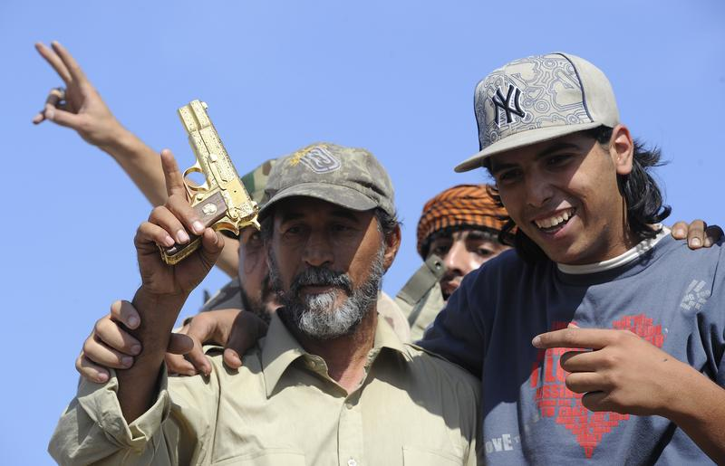 Libyan National Transitional Council (NTC) fighters hold what they claim to be the gold-plated gun of ousted Libyan leader Moamer Kadhafi