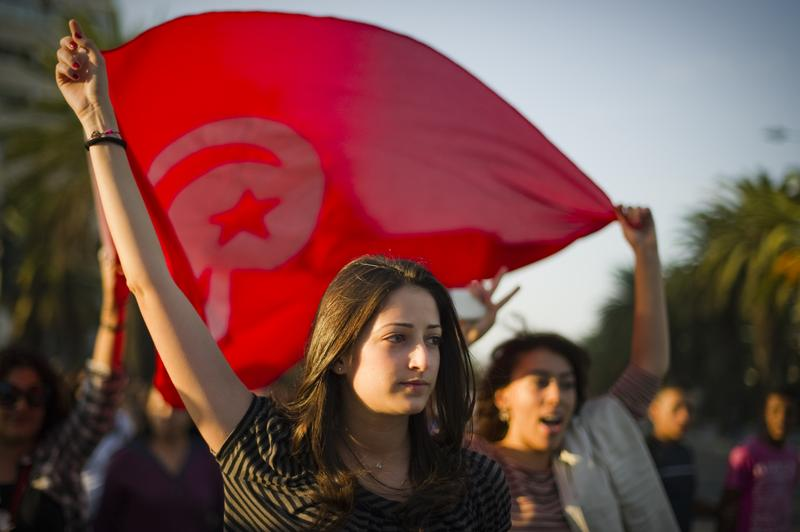 Young Tunisian girls hold a giant flag as people demonstrate.