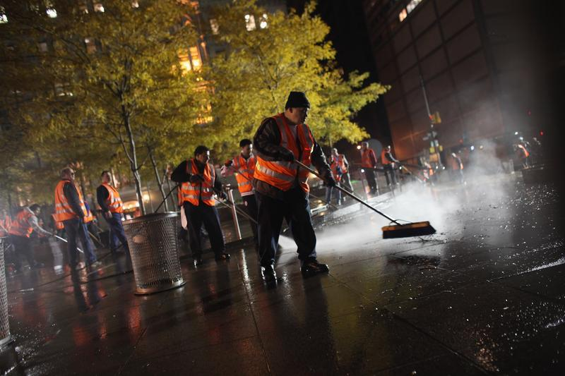 Workers clean up Zuccotti Park after New York City police in riot gear removed Occupy Wall Street protesters early on November 15, 2011 in New York.