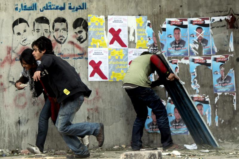 Egyptian protesters run for cover during clashes with riot police at Cairo's landmark Tahrir Square on November 20, 2011. Several hundred Egyptians occupied Cairo's Tahrir Square with sporadic clashes