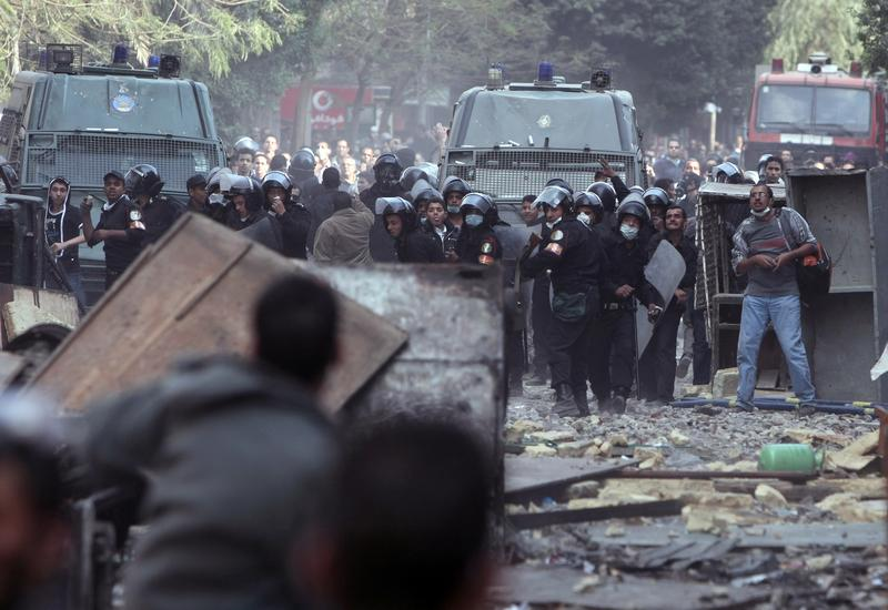 Egyptian protesters take cover during clashes with riot police along a road which leads to the Interior Ministry, near Tahrir Square, in Cairo on November 23, 2011.
