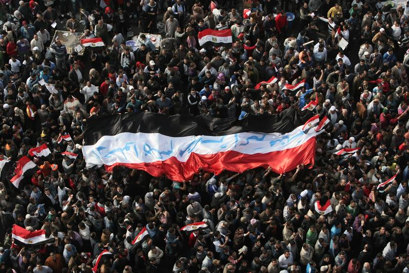 Egyptian demonstrators hold up a huge national flag with the slogan 'Leave, Egypt is bigger than all of you' written on it in Arabic in Cairo's Tahrir square on November 25, 2011.