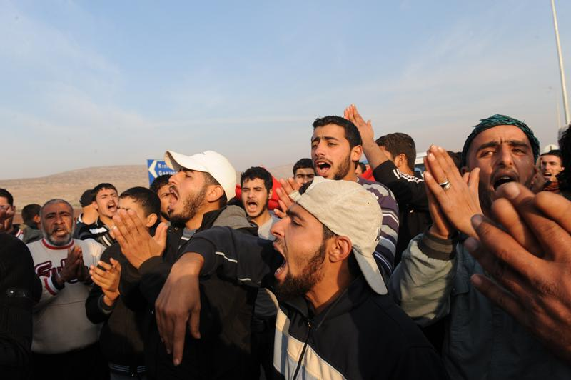 Syrian refugees demonstrate on December 5, 2011 in a camp near the Turkish border town of Reyhanli after Turkish authorities expelled two Syrian refugees back to their country .