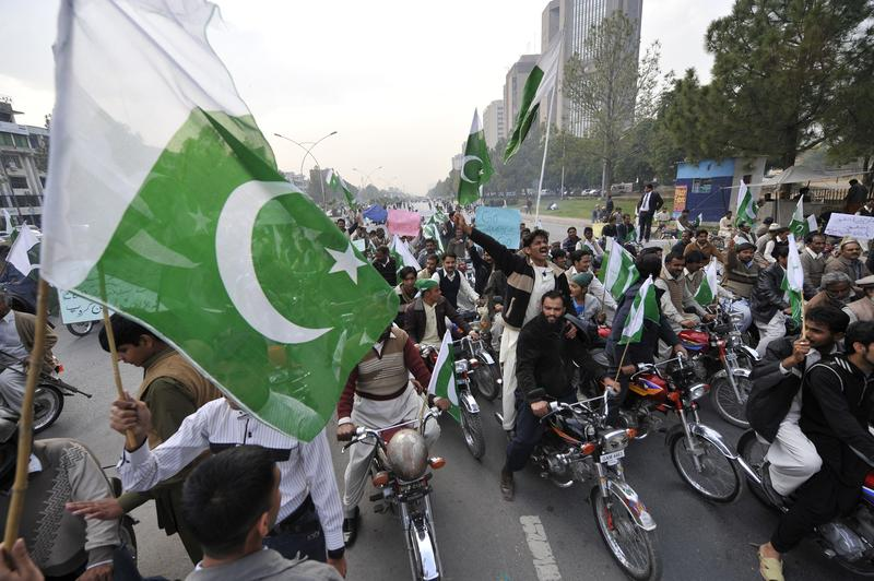 Pakistani protesters carry national flags during a demonstration in Islamabad on December 8, 2011 against the cross-border NATO air strike on Pakistani troops.