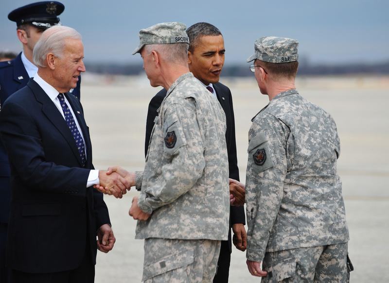 President Barack Obama and Vice President Joe Biden greet returning troops as they step off a plane before attending a ceremony to mark the return of the US Forces - Iraq colors December 20, 2011.