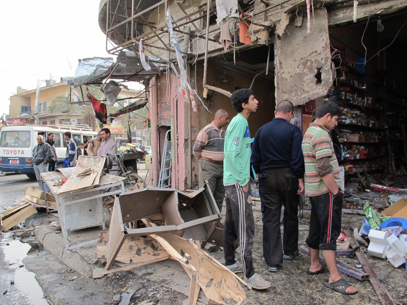 Iraqis inspect the damage after a wave of attacks in Baghdad killed at least 57 people.