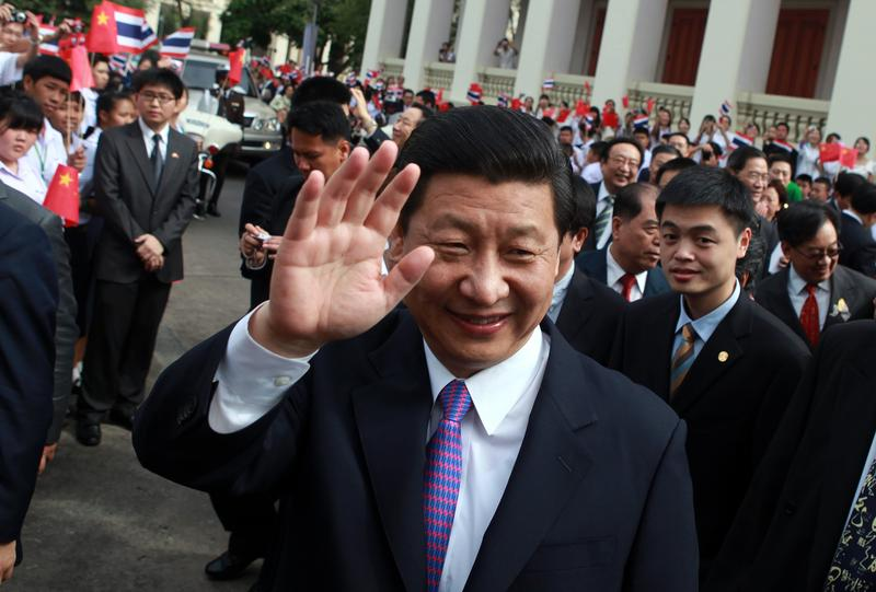 Then-Vice President of China Xi Jinping waves to Thai students during a visit to Chulalongkorn University in Bangkok on December 24, 2011.