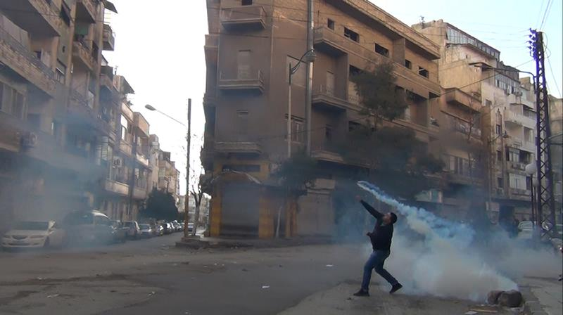 A protester in the flahspoint central Syrian city of Homs throws a tear gas bomb back towards security forces, on December 27, 2011. Syrian police used tear gas to disperse some 70,000 people in Homs.