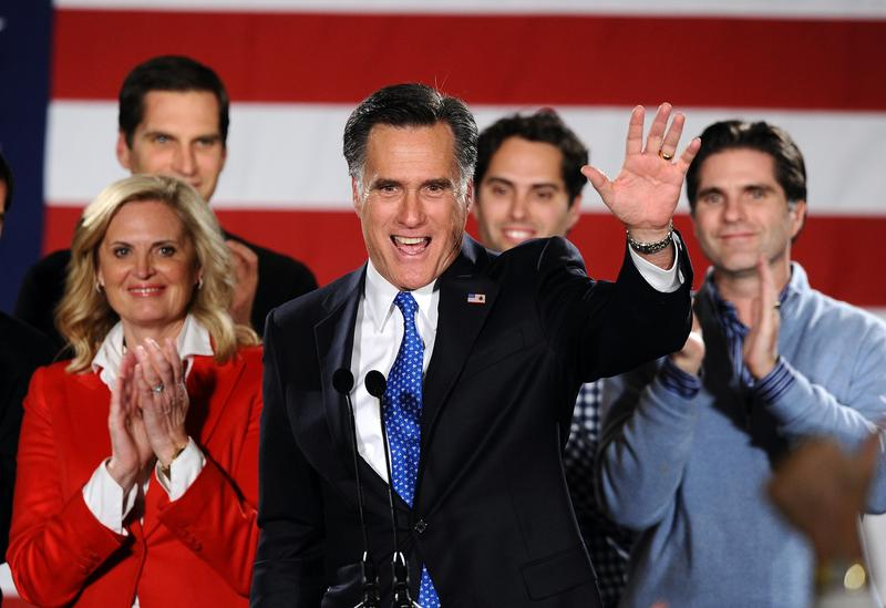 Republican presidential hopeful Mitt Romney (C) waves to his supporters during his caucus night rally following republican caucuses in Des Moines, Iowa, on January 3, 2012.