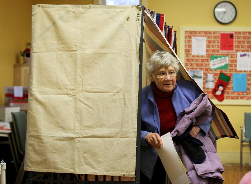 Voter Julie Runnells comes out from a voting booth at a polling station in Concord, NH.
