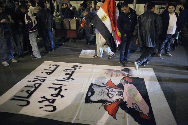 A caricature of Syrian President Bashar al-Assad is spread on the ground as Syrian people demonstrate outside the Arab League building on January 22, 2012 in Cairo Egypt.
