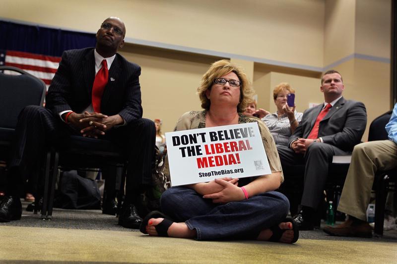 People listen as Republican presidential candidate Newt Gingrich speaks in Jacksonville, Florida.