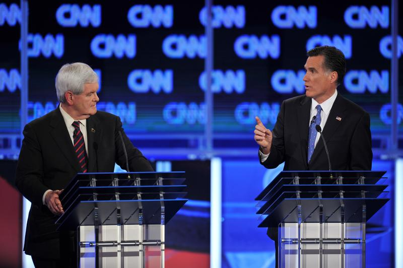Republican presidential candidates Newt Gingrich listens to former Massachusetts governor Mitt Romney.