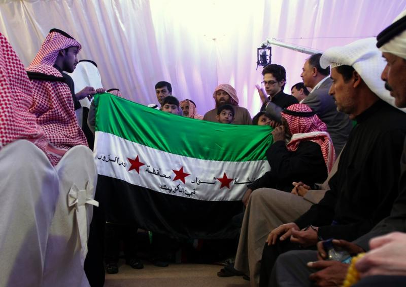 Syrian children hold up Syria's pre-Baath national flag, adopted by the anti-regime uprising.