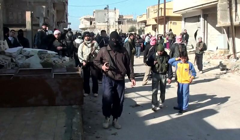 An image taken from YouTube on January 28, 2012 shows armed men, said to be members of the Free Syrian Army (FSA), standing guard during an anti-regime protest in the central town of Rastan.