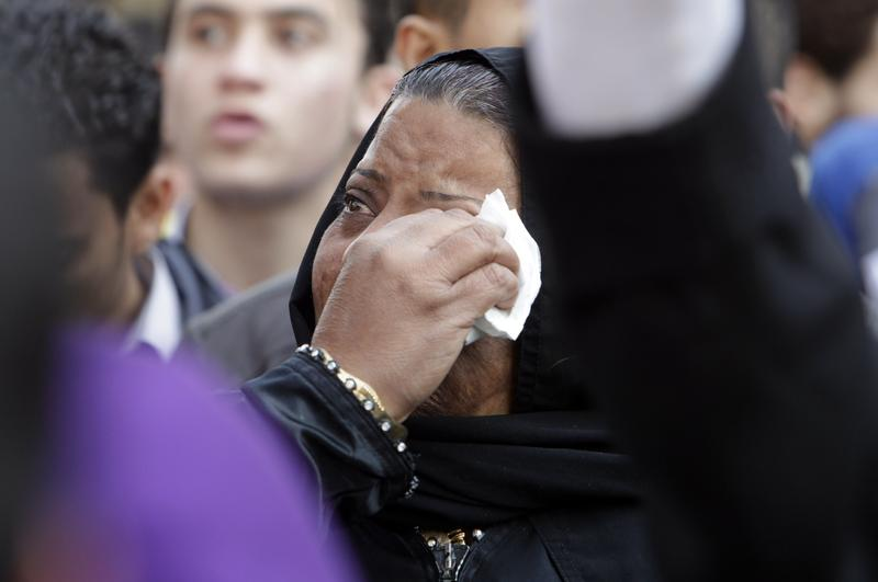 A tearful woman wipes her tears as protesters gather to demonstrate outside Cairo's Al Ahly football stadium.