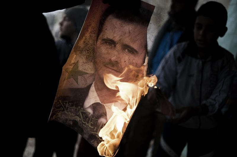 A member of the Free Syrian Army holds a burning portrait of embattled President Bashar al-Assad.