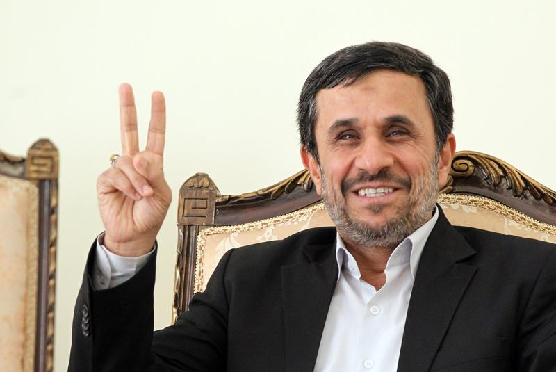 Iranian President Mahmoud Ahmadinejad flashes the V-sign for victory as he waits for the arrival of Ismail Haniya, Palestinian Hamas premier.