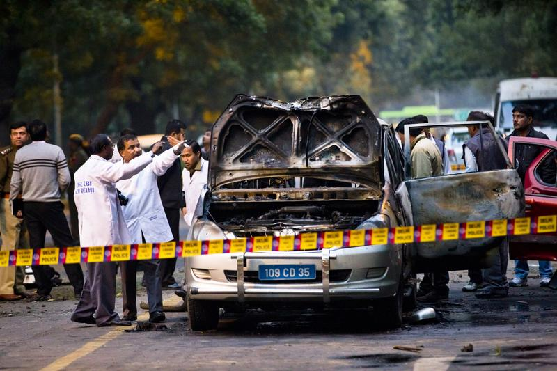 Police examine a damaged Israeli embassy vehicle after an explosion in New Delhi, India.
