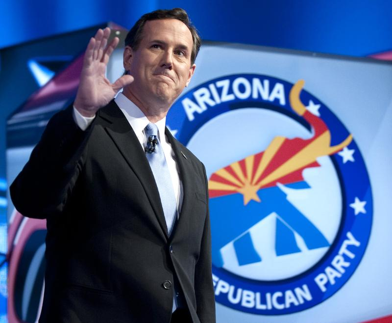 Rick Santorum waves as he arrives to the debate hall in Mesa, Arizona.