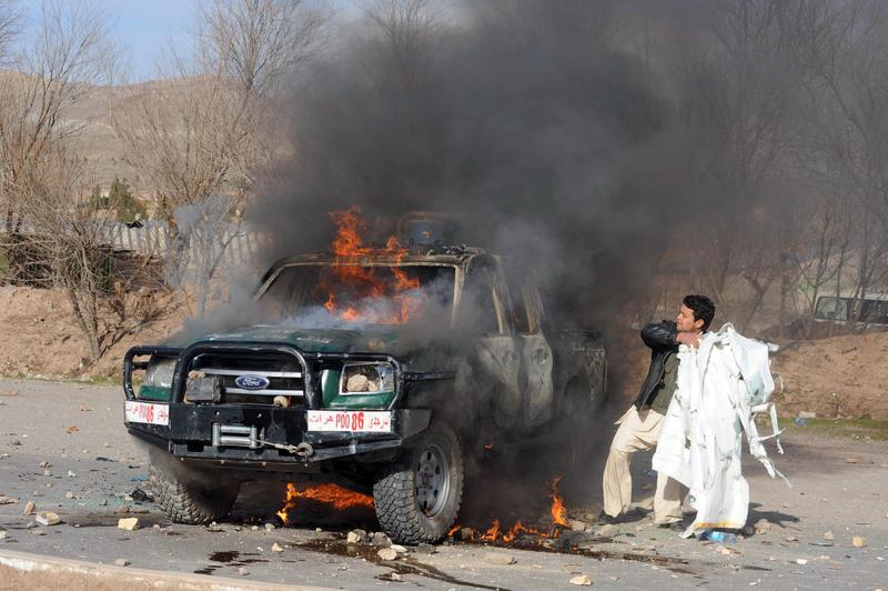 An Afghan demonstrator adds flammable material to a burning police vehicle.