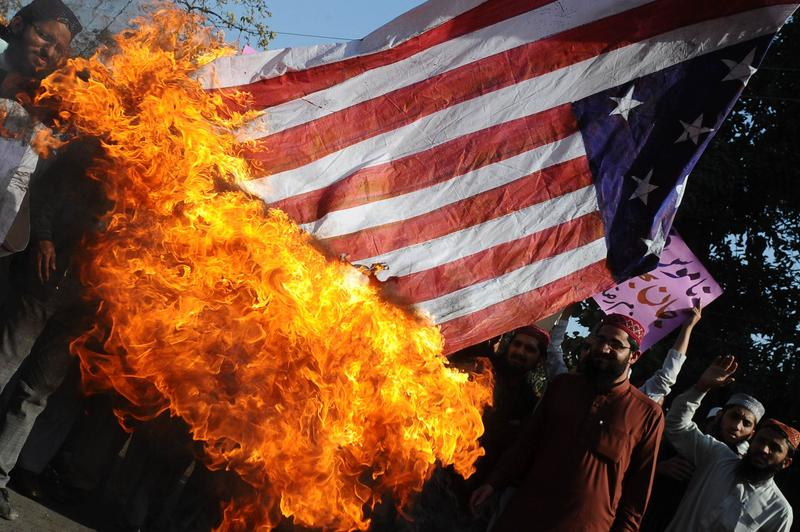 Activists of Majlis Ulma Nzamia Pakistan burn a US national flag during a protest in Lahore, Pakistan.