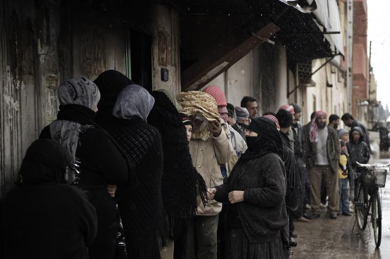 Syrians queue for bread outside a bakery in Qusayr, nine miles from Homs.