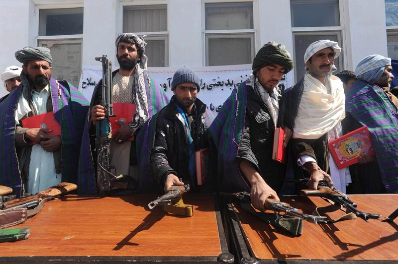 Taliban fighters stand with their weapons.