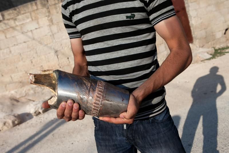 A Syrian citizen holds the remains of a projectile shot by a tank near the town of Khan Sheikhun.