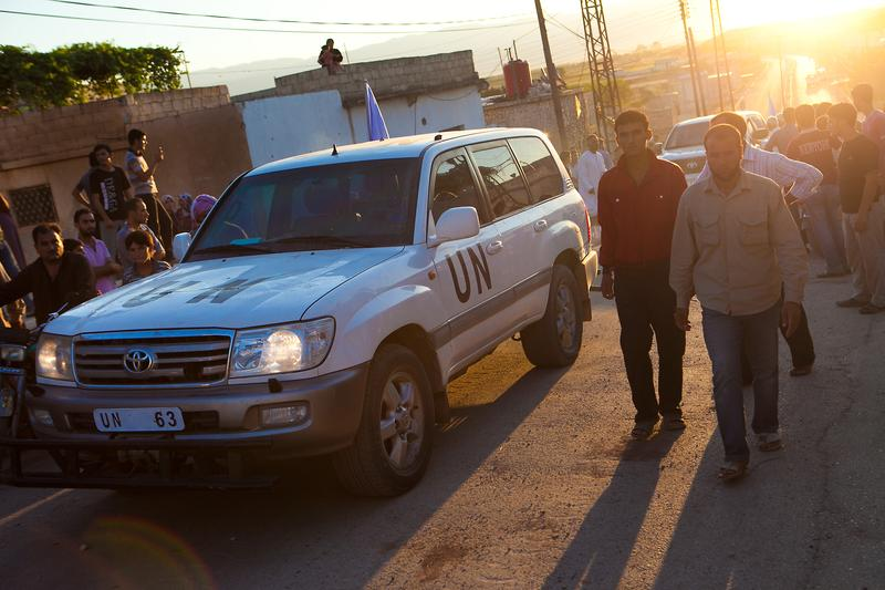 Residents of the Syrian village of Treimsa gather around the vehicles of UN observers upon their arrival to investigate an attack on the village.