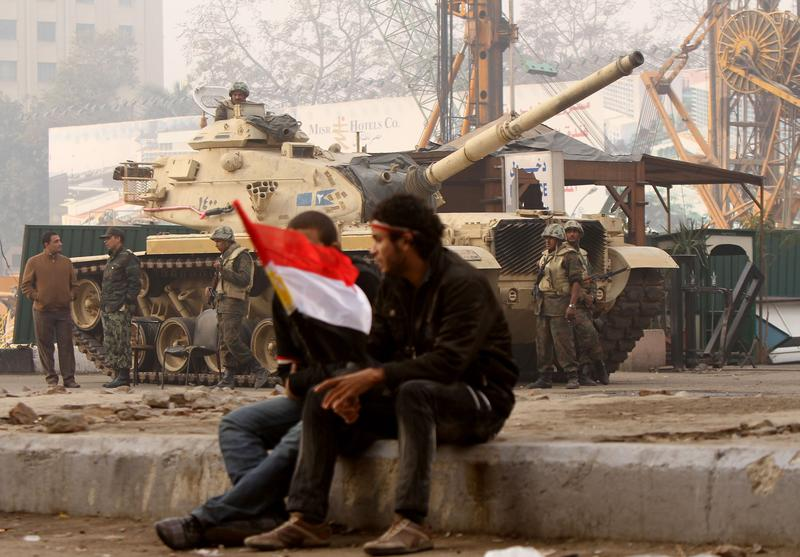 Egyptian anti-government protesters sit near an army tank as they gather outside the state television building in Cairo on February 11, 2011