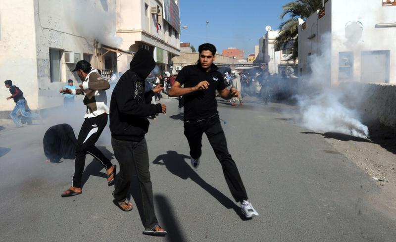 Bahraini protestors run for cover after police fired tear gas canisters to disperse them in the village of Diraz, northwest of Bahrain, on February 14, 2011