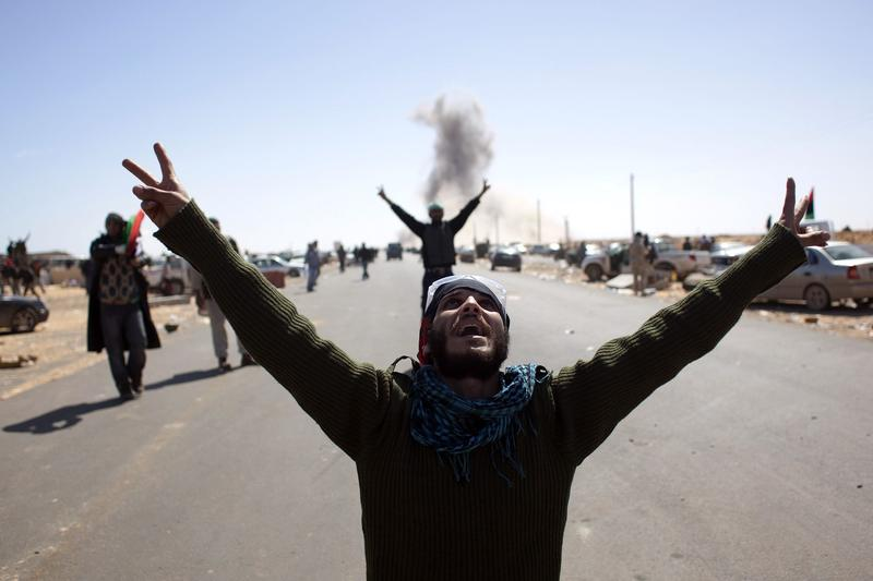 Libyan rebel fighters flash the victory sign as they look at an airforce fighter jet flying overhead after dropping a bomb near a checkpoint on the outskirts of the oil town of Ras Lanuf on March 7, 2