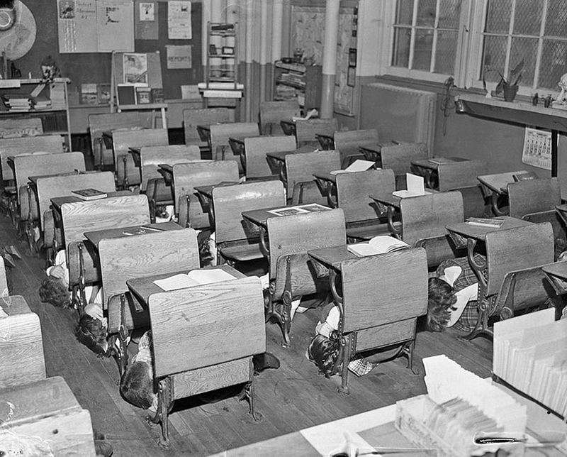 "Schoolchildren in the 1950s practice ""duck and cover"" in an atomic bomb drill."