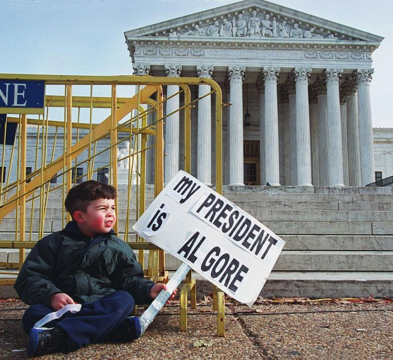 (FILE) Four-year-old Miles Slentz from Aberdeen, Maryland, takes a rest and watches his two elder sisters and parents protest in front of the US Supreme Court, 13 December 2000.