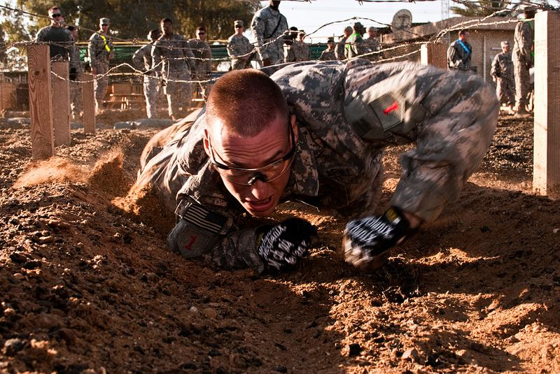 Sgt. Derek Czerniak, serving on Camp Taji, Iraq, with the Enhanced Combat Aviation Brigade, 1st Infantry Division, crawls under a barbed wire obstacle during a combat skills competition, 11/7/2010