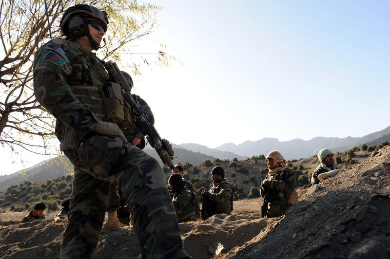 A U.S. Army Special Forces Soldier watches Afghan Commandos while patrolling a village in Paktia province, Afghanistan near the Pakistan border, on Nov. 30.