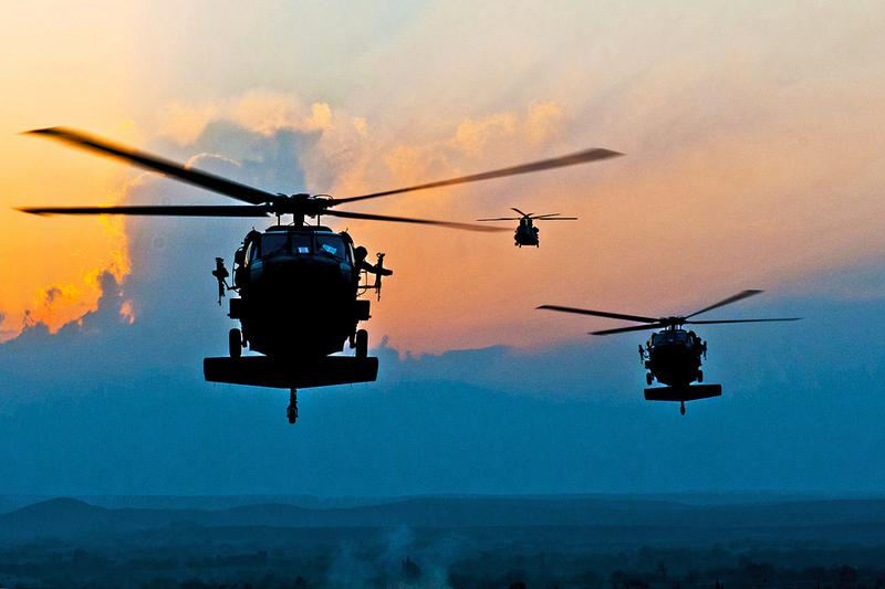 As the sun heads toward the horizon, two UH-60 Black Hawks and a CH-47 Chinook prepare to land at Forward Operating Base Connolly in eastern Afghanistan, Dec. 7, 2010