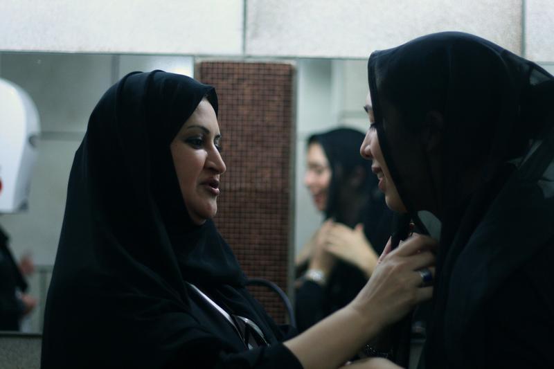 Two women adjust their hijabs in Saudi Arabia.