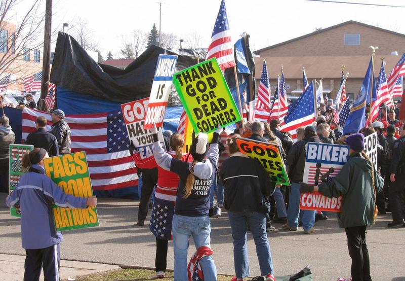 Members of the Kansas-based Westboro Baptist Church wave signs in front of a group of flag-waving bikers acting as human shields for a family holding a funeral for their son in Flushing, MI. (2006)