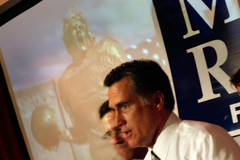 Republican presidential candidate and former Massachusetts Gov. Mitt Romney speaks to the media as a television ad plays behind him.