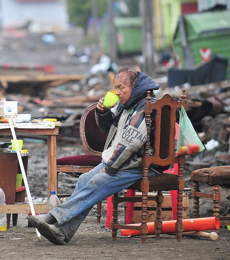 Man drinks in a street devastated by the tsunami in Talcahuano, Chile
