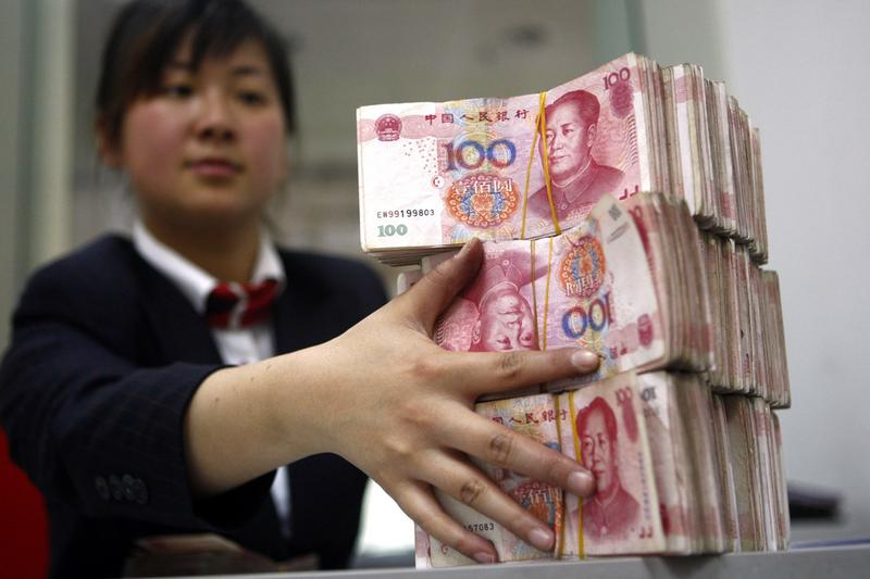A Chinese bank worker arranges stacks of 100-yuan notes.