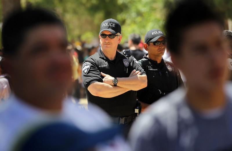 Police watch as opponents of Arizona's new immigration enforcement law gather outside the state capitol building.
