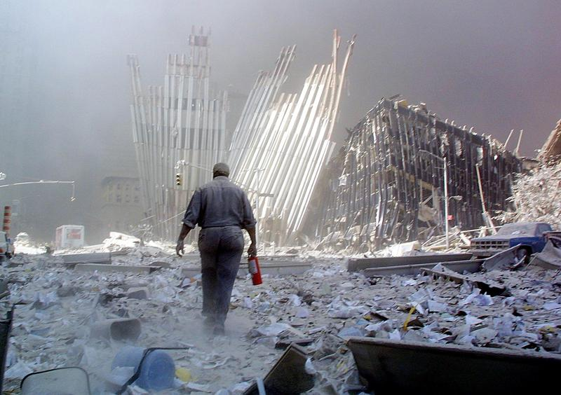 A man with a fire extinguisher walks through rubble after the collapse of the first World Trade Center Tower 11 September, 2001, in New York. The man was shouting as he walked looking for victims who