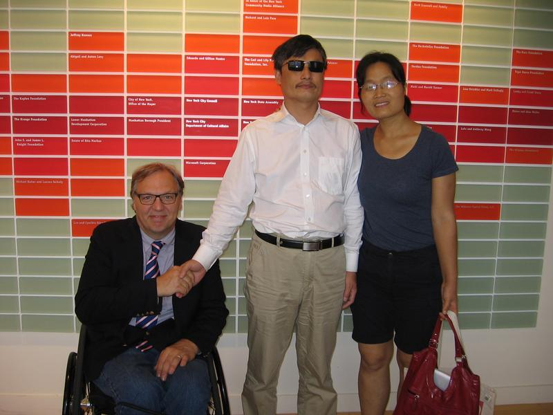 Guangcheng poses with his wife and John Hockenberry.