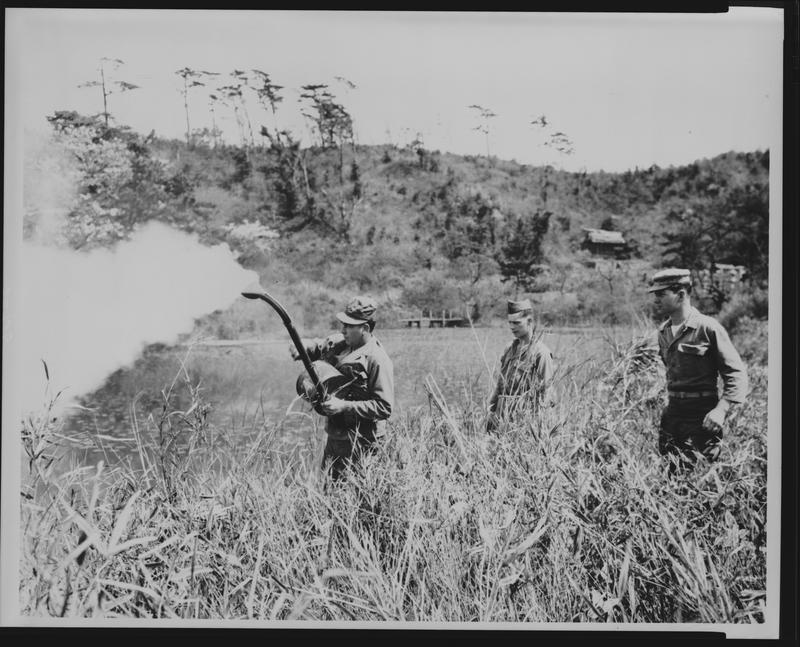 Corp. Thomas Lindsay, 28th Malaria Control Detachment, demonstrating the use of a hand rotary blower to drift a cloud of DDT dust to combat mosquitoes, Yokohama, Japan. April 1949.