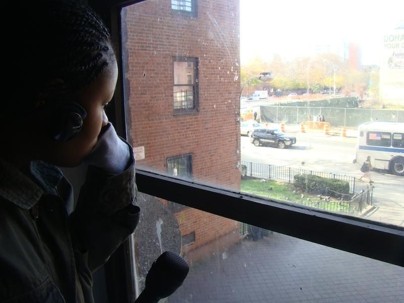 Temitayo Fagbenle looks out the window of a public housing building